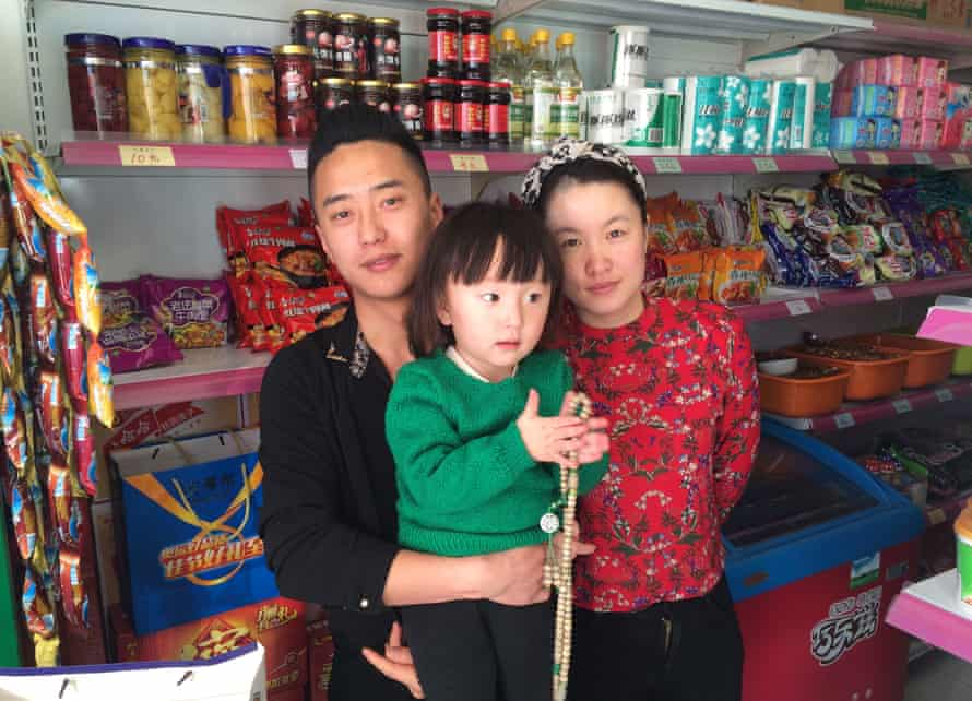 Shopkeeper Zhou Fei and his wife Bao Shan with their young daughter.