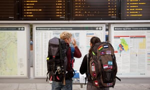 backpackers checking train timetables in a station