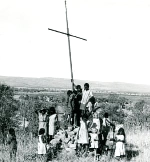 Children stand below a wooden cross on a pile of stones