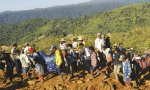 Jade mine workers and rescue teams carry victims of the landslide in Hpakant, Myanmar.