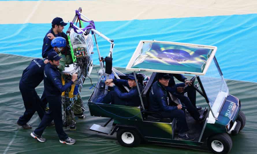 Juan Pinto in an exoskeleton is helped onto the field during the Opening Ceremony of the 2014 FIFA World Cup Brazil.