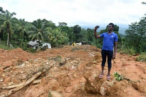 A local man photographs the site of a mudslide in the Kiribathgala village in Ratnapura district