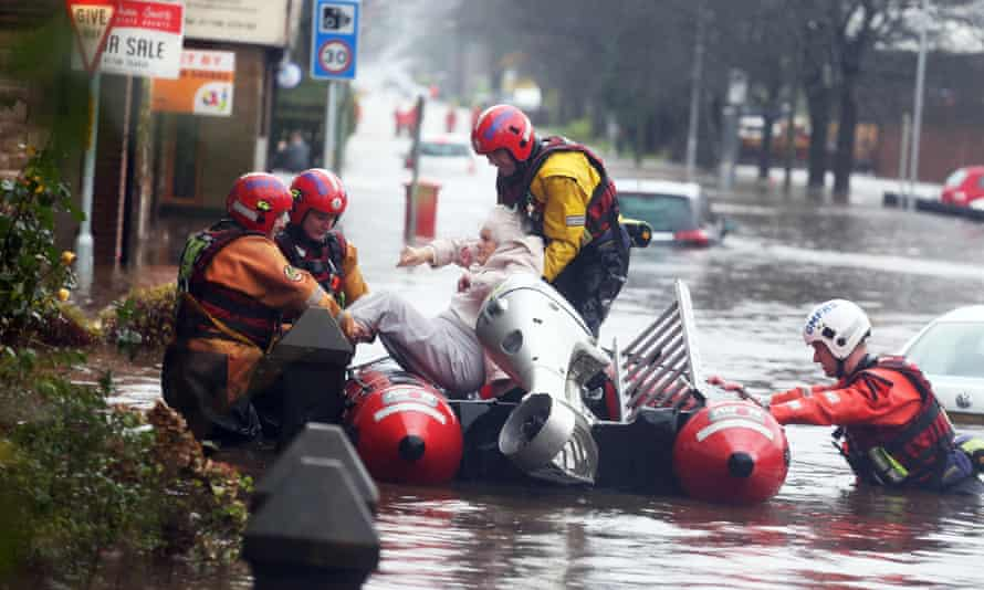 Fire and rescue services evacuate a woman from her flooded home in Littleborough, Greater Manchester