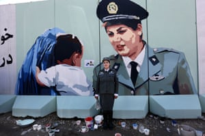 Kabul, Afghanistan Friba Hameed, 30, an Afghan police officer, poses for a photograph in front of a mural of herself, painted by an independent artist, outside the main gate of a police precinct