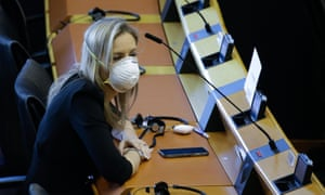 A member of European Parliament wearing protective masks and gloves attend a mini plenary session of European Parliament in Brussels, Belgium, on March 26, 2020.