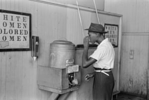 A man drinking at a 'colored' water cooler at a bus terminal in Oklahoma City in July 1939.