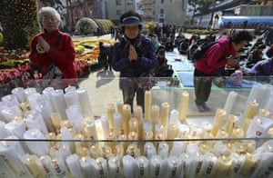 Women pray during a special service to wish their family members success in the college entrance exams at the Jogye temple in Seoul, South Korea.