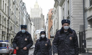 Russian police officers patrol an almost empty Arbat street in Moscow on Thursday.