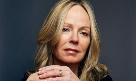 Dani Shapiro, with long, blonde hair, looking at the camera, with her hands folded beneath her chin