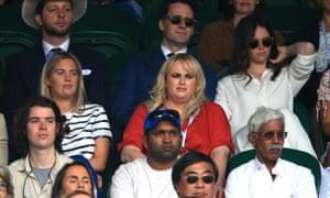 Rebel Wilson (in red) sat alongside fellow actor Felicity Jones (right) at Wimbledon on Monday.