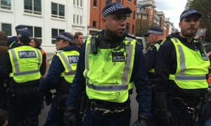 Police with paint spattered uniforms on Vauxhall Bridge Road.