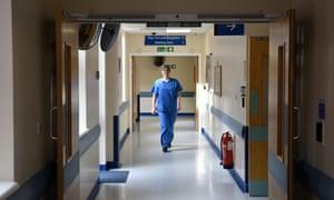 A member of clinical staff walks along a corridor