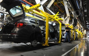 A worker constructs cars at Vauxhall's Ellesmere Port plant