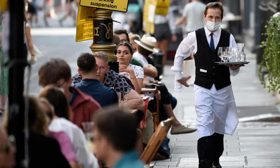 A waiter serves customers at tables outside a restaurant in Soho, London