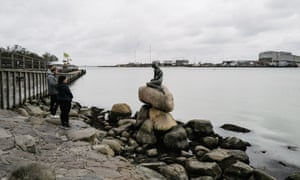 A couple view the number one tourist attraction in Copenhagen, The Little Mermaid, during the coronavirus precautions in Copenhagen, Denmark on 1 April 2020.