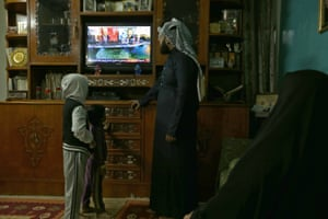 An Iraqi family follows the US presidential elections on television at their home