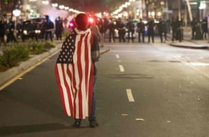 A protester wearing an American flag faces police during a protest in Oakland, California