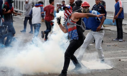 A demonstrator throws back a teargas canister during clashes with government security forces in Caracas on Tuesday.