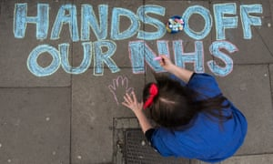 Woman writing hands off the NHS on the ground