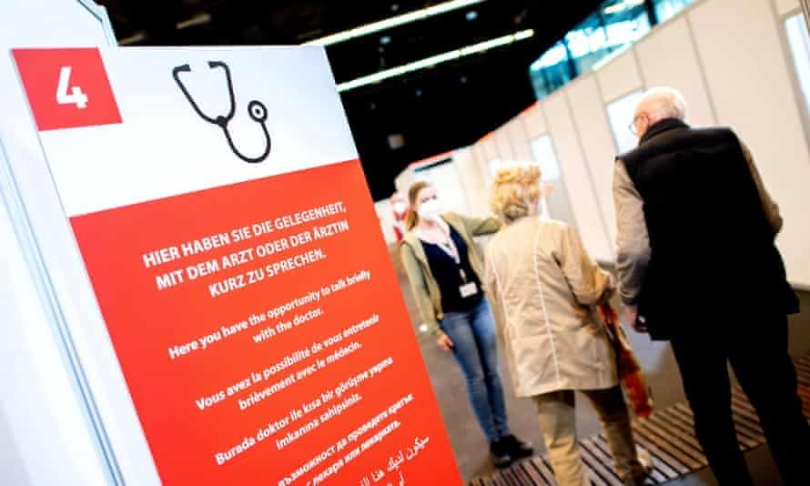Two people being shown to a booth in the background with a large red medical information sign in the foreground