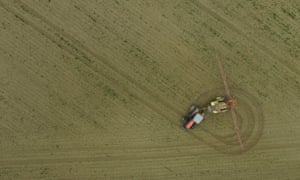 A tractor spreads pesticide on a field near Prenzlau, Germany