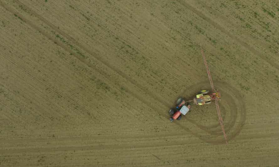 A tractor spreads pesticide on a field near Prenzlau, Germany