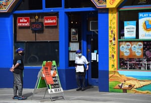 Restaurant employees wearing masks look on while waiting for customers in the Haight Ashbury area of San Francisco.