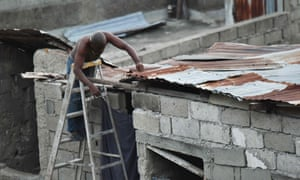 A man repairs part of his roof in preparation for the arrival of Hurricane Irma in Lauriers neighborhood of Cap-Haitien