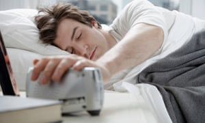 A young man in bed, eyes closed, his hand over an alarm clock to switch it off