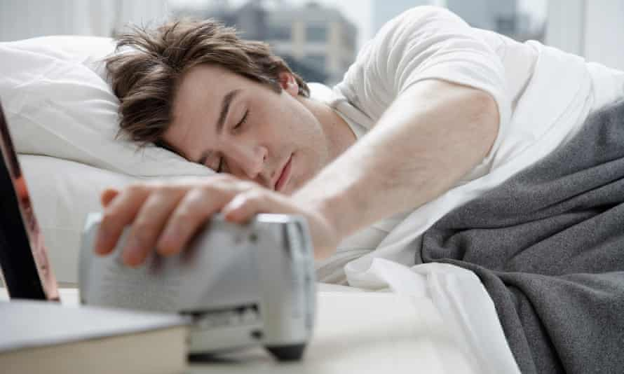 Young man switching alarm clock off