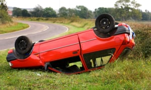 Crashed red hatchback car upturned on its roof by a bend in the road