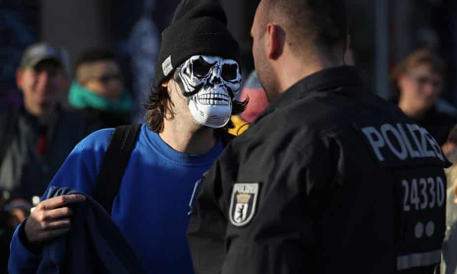 'They are part of something that is really frightening people' … a masked protester and a policeman.