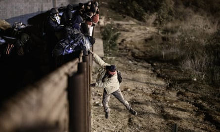 A person jumps a border fence to get into San Diego, California from Tijuana, Mexico on 1 January.