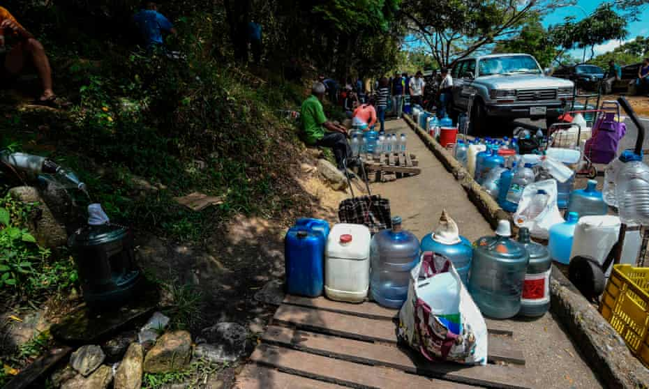 People gather to collect water in Caracas on Sunday.