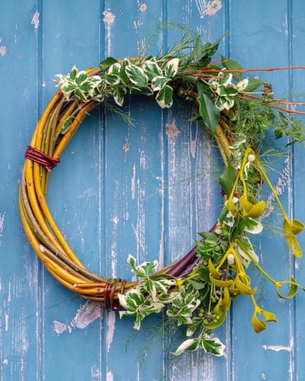 Handmade Christmas wreath made from hedgerow materials hanging on a blue door
