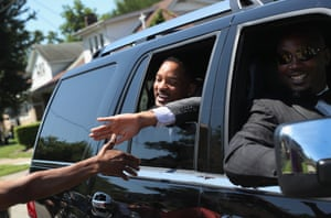 Actor Will Smith greets the crowds while riding in the funeral procession