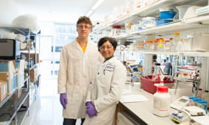 eric minikel and sonia vallabh in lab coats at a work bench in the broad institute