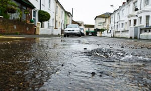 Water leak in the middle of a residential road caused by a burst water main.