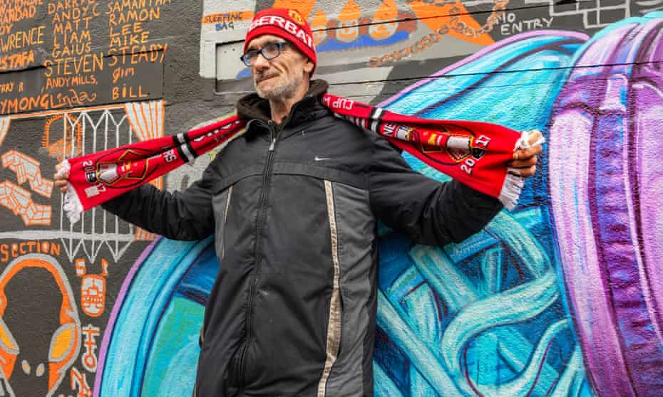 Grandad, one of the 33 artists behind the Doodle on Ducie Street mural, stands in front of the work.