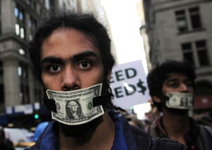 Head shot of an Occupy Wall Street protester in New York, October 2011, with a dollar bill taped across his mouth