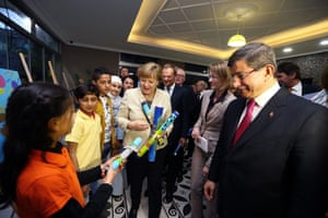 Davutoğlu and Merkel speak with children as they visit a Syrian refugee camp in Nizip, Gaziantep