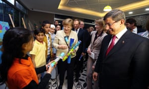 Turkey's then-prime minister, Ahmet Davutoğlu (R), the German chancellor, Angela Merkel (L), and the EU council president, Donald Tusk (behind), meet children at a refugee camp in Turkey in April.