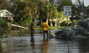 People walk through flooded streets the morning after Hurricane Irma swept through Fort Myers, Florida.