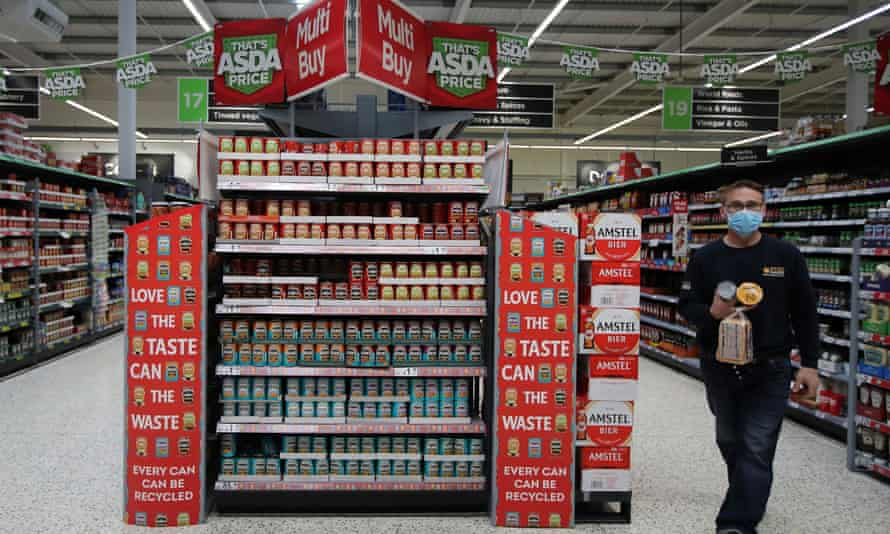 A customer walks the loose tins in the UK supermarket Asda