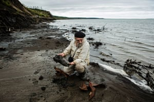"""Sergey Zimov, a scientist, digs up mammoth and bison bones at Duvanny Yar, a permafrost """"megaslump"""" or a thermokarst depression. The area is an important scientific destination for scientists studying permafrost thaw, as well as the history of late Pleistocene era Beringia land, with thousands of years of historical and climate information located in the layers of crumbling soil."""