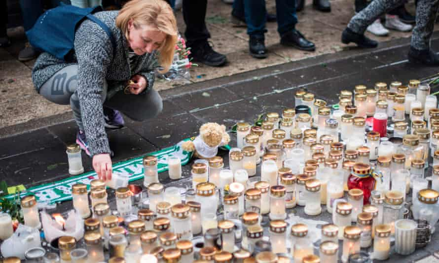 A woman lights a candle to commemorate the victims of the terror attack at a makeshift memorial near the site in Stockholm.