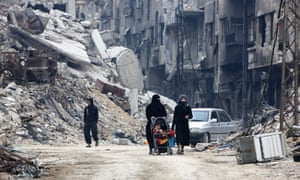 Civilians walk along a destroyed street in the town of Harasta in eastern Ghouta.