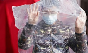 A passenger wearing a mask and covered with a plastic bag walks outside the Shanghai railway station.