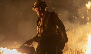 A firefighter uses a drip torch to start a backfire near Somis, California.