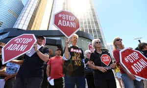 Anti-Adani protesters hold signs outside the company's offices in Brisbane